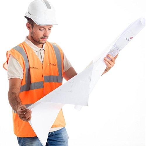 Conducteur de travaux étudiant un plan de chantier.